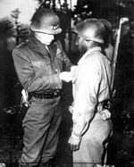 Lieutenant General Patton of the US 3rd Army awarding the Silver Star medal to Private Ernest Jenkins for gallantry during actions at Chateaudun, France, 13 Oct 1944