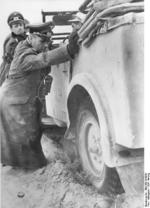 Colonel General Erwin Rommel and General Siegfried Westphal helping with pushing a stuck vehicle, North Africa, early 1941