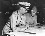Richmond Turner and Alexander Vandegrift aboard USS McCawley looking at maps of the Tulagi-Guadalcanal operation in the Solomon Islands, circa Jul-Aug 1942