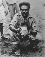 Jacob Vouza holding the severed head of a Japanese soldier, date unknown