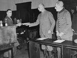 Wilhelm List receiving his indictment during the Hostage Trial, Nürnberg, Germany, 12 May 1947; note Maximilian von Weichs next to List