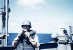 Lieutenant Howard W. Whalen holding binoculars aboard USS Sanborn, 1945, photo 1 of 2