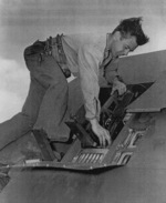 Aviation Ordnanceman 1st Class Billy Simms inspecting the wing guns of a fighter aircraft aboard USS Anzio, 18 Apr 1945