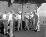 Captain George C. Montgomery shaking hands with men under his command aboard USS Anzio, 23 May 1945