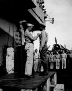 US Navy Captain Herbert W. Taylor of USS Cowpens awarding African-American Stewards Mate 3rd Class Fred Magee, Jr. with commendation of the Secretary of the Navy, Oct 1944