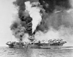 HMS Formidable burning after being struck by a Japanese special attack aircraft in the Pacific Ocean off Sakishima Islands, Japan, 4 May 1945