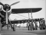 Sailors pushing an armed Albacore aircraft of No. 820 Squadron FAA into position aboard HMS Formidable, off North Africa, Nov 1942