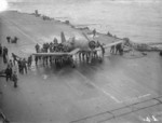 Crewmen aboard HMS Formidable pushing a damaged Corsair fighter which had just landed, off Norway, Aug 1944. Note the prop with one blade badly bent.