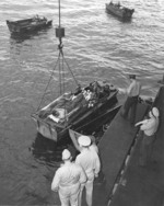 Wounded personnel being loaded from USS Intrepid into waiting LCVP landing craft, probably at Ulithi, Caroline Islands, 1944, photo 2 of 2
