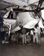Ordinancemen loading a 1,000-pound bomb into the bombay of a TBM-1C aboard USS Intrepid, 1943-1945; note flame arrester on the plane