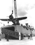 Brewster F2A-3 Buffalo being lifted aboard aircraft transport USS Kitty Hawk at Pearl Harbor, Hawaii, May 1942. Note open hangar bay in the stern of the ship.