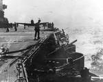 Damage to Lexington port side number six 5-in gun by dive bomb, Battle of Coral Sea, 8 May 1942, photo 2 of 2; note TBD-1 Devastator bomber on deck and F4F-3 Wildcat fighter approaching to land