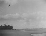 US Navy LST-134 beached at Normandy, France while unloading during low tide, 12 Jun 1944; note barrage balloons overhead providing protection from air attack and DUCKs on the beach