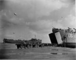 US Navy LST-134 and LST-325 beached at Normandy, France as jeeps driving along the invasion beach carry casualties to the waiting vessels, 12 Jun 1944, photo 1 of 4