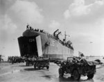 US Navy LST-134 and LST-325 beached at Normandy, France as jeeps driving along the invasion beach carry casualties to the waiting vessels, 12 Jun 1944, photo 2 of 4