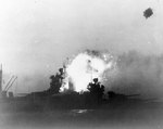 New Mexico hit by a Kamikaze special attack aircraft at dusk off Okinawa, 12 May 1945; photo taken from cruiser Wichita