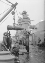 Sailors aboard HMS Rodney receiving a 16-inch shell from an ammunition ship, 1940, photo 1 of 2