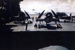 F6F-3 Hellcat fighters on the flight deck of Saratoga as a TBM Avenger approached to land, circa 1943-44