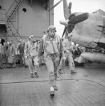 US Navy pilots Ensign Charles Miller, Lieutenant (jg) Henry Dearing, and Lieutenant (jg) Bus Alber walking toward their aircraft aboard USS Saratoga, 5 Nov 1943; note F6F fighter