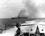 Carrier Ticonderoga burning after being struck by kamikaze aircraft off Taiwan, 21 Jan 1945; note light cruiser Miami