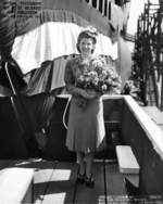 Mrs. Davenport, wife of future commanding officer of Trepang, posing with the submarine at its christening, Mare Island Naval Shipyard, California, United States, 23 Mar 1944
