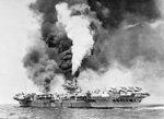 HMS Victorious on fire after being struck by Japanese special attack aircraft, off Sakishima Gunto (Islands), Japan, 9 May 1945