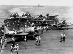 SBD-3 Dauntless, F4F-4 Wildcat, and TBF-1 Avenger aircraft aboard USS Enterprise, northeast of Nouméa, New Caledonia, 2 May 1943; note USS Washington in background