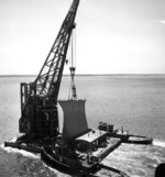 The bow of USS Kentucky being transported on a crane en route between Newport News to Norfolk, Virginia, United States, to be fitted on USS Wisconsin, circa May-Jun 1956