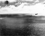 Zuikaku settling as she sinks, 25 Oct 1944; profile of an Avenger is seen flying overhead
