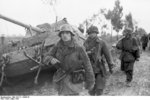 German MG42 machine gun crew passing a wrecked Elefant tank destroyer, Nettuno, Italy, Mar 1944