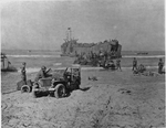 LST unloading vehicles and supplies on the beach in Gela, Sicily, Italy, Jul 1943; note Ford GPW Jeep in foreground