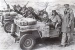 A close-up of a British heavily armed patrol of L Detachment SAS in their jeeps, just back from a three month patrol, 18 Jan 1943; note twin-mounted Vickers K machine guns and F-S dagger; photo 2 of 3
