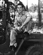 USAAF photographer Jack Heyn sitting atop a jeep, 1943