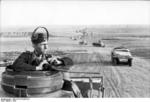 A German soldier with headphones and binoculars at an open hatch of a tank, Southern Russia, mid-1942; note SdKfz. 251 halftrack vehicles and Panzer II tanks in background