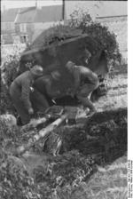 German soldiers preparing to attach an anti-tank gun to the hitch of a SdKfz. 251 halftrack vehicle, France, 21 Jun 1944