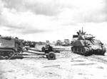 M4 Sherman tanks and halftrack vehicles towing M3 37-mm anti-tank guns on either Omaha or Utah Beach, Normandy, France, 12 Jun 1944