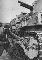 Japanese tanker clearing mud from the tracks of a Type 89 I-Go medium tank, China, late 1937 to early 1938