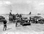 LCT-550 landing Dodge WC54 field ambulances of the 546th Medical Company at Normandy, France, Jun 12, 1944; note snorkel tube for fording streams on lead ambulance.
