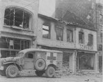 American ambulance waiting outside a bombed building in Bastogne, Belgium while a searcher looked for persons injured during the ten-day defense by US 101st Airborne Division, 26 Dec 1944