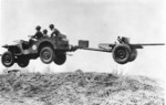 Bantam Jeep, towing a 37 mm Gun M3 piece, jumping over a small hill, New River, North Carolina, United States, 1941