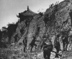 Japanese troops scaling a wall, China, late 1937 to early 1938