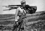Chinese soldier carrying captured Japanese Type 38 rifles and a Type 11 light machine gun, date unknown