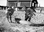 Two British soldiers inspecting an unexploded German bomb at the railway station at Grong, near Namsos, Norway, 30 Apr 1940; note Lee-Enfield No. 4 rifles