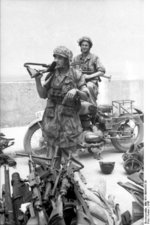 German paratroopers with FG 42 rifle and MP 40 submachine gun in Italy guarding a cache of captured weapons, 1943